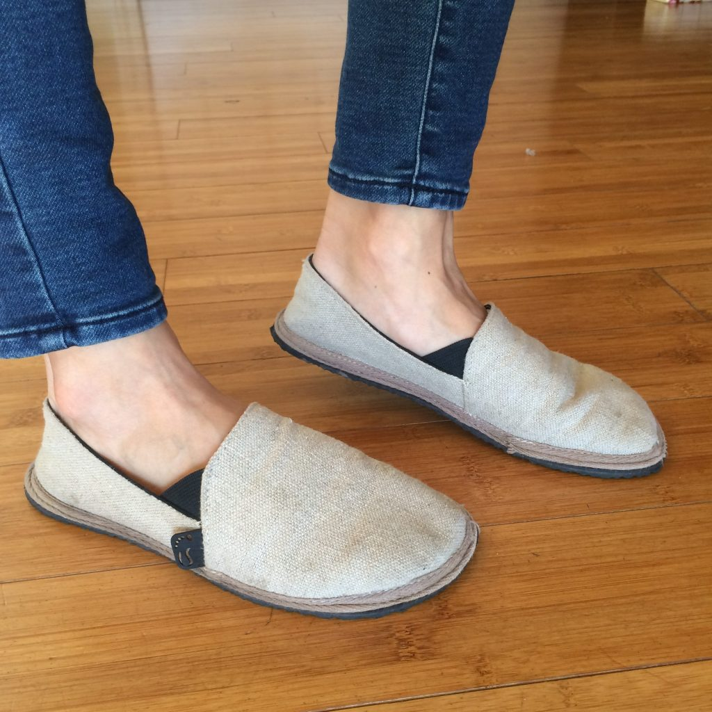 A pair of feet from the side wearing the Unshoes Terra Vida vegan hemp barefoot slip ons in natural color