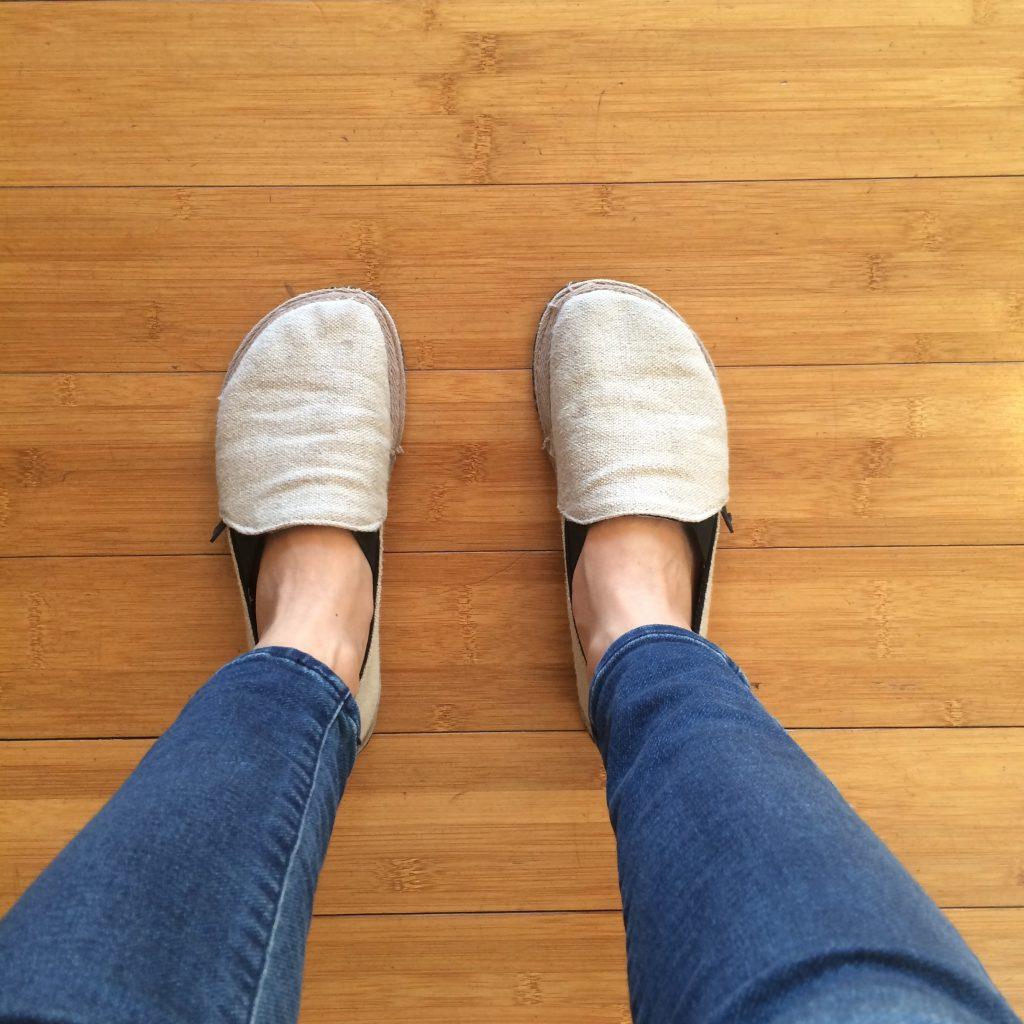 Unshoes Footwear Terra Vida canvas hemp barefoot slip on shoes shown on a pair of feet standing on wood