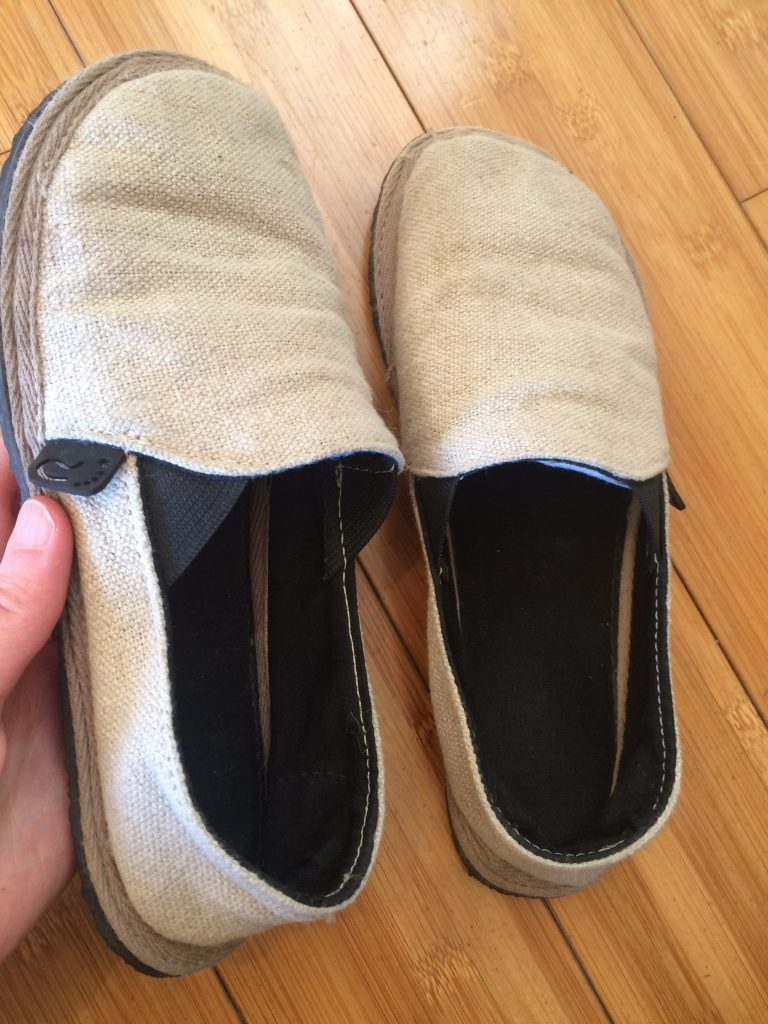 A hand holding up an Unshoes Terra Vida vegan hemp barefoot slip on shoe to show the logo and elastic panelling