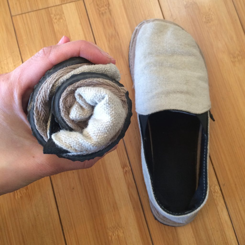 A hand holding a rolled up unshoes terra vida barefoot vegan hemp slip on to review the flexibility of the shoe