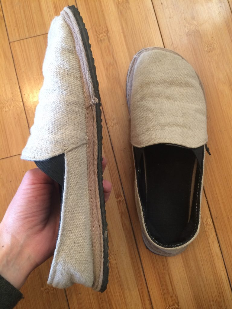 A hand holding an unshoes terra vida barefoot vegan hemp slip on showing the top stitch construction and thin sole