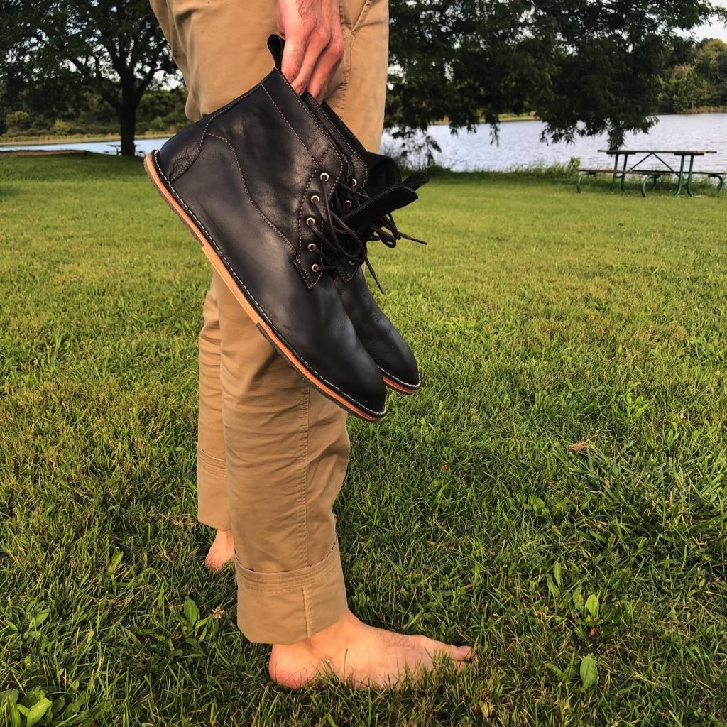 A man standing barefoot holding a pair of barefoot dress shoes by DaVinci Footwear - the Lapworth boot in waxed black.