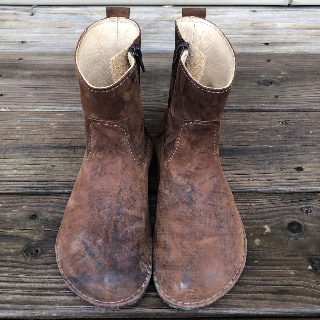 A pair of Luks Primavera barefoot ankle boots standing on a wet deck.