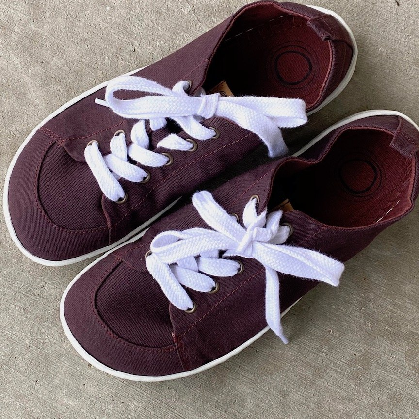A pair of Mukishoes vegan casual barefoot sneakers in Plum color sitting on concrete