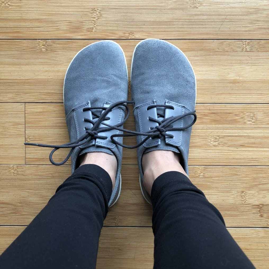 top down view of feet wearing Zaqq Piquant barefoot casual sneakers in grey on wood floor