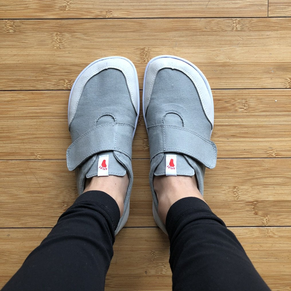 a close up top down view of feet in Splay Athletics hammerhead velcro sneakers on wood floor