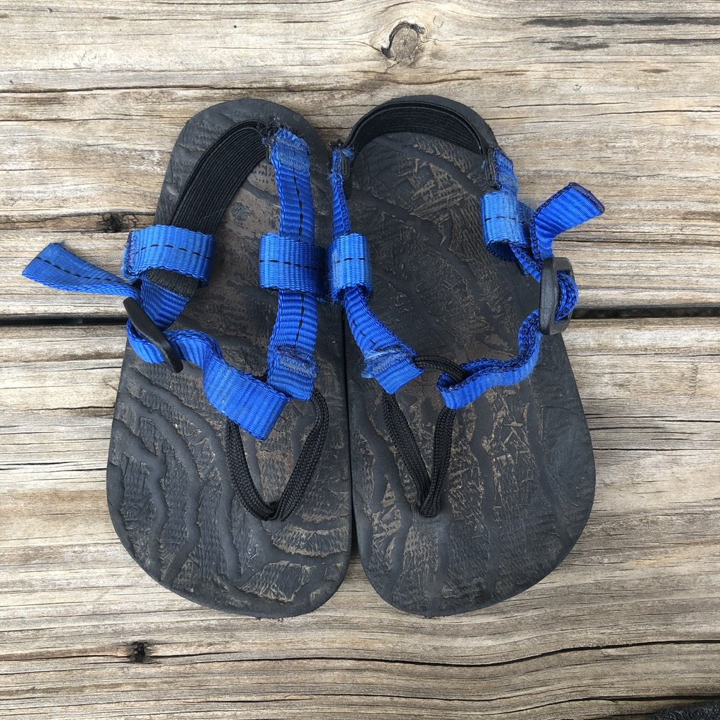 a pair of Unshoes Keota sandals for kids sitting on a wood deck