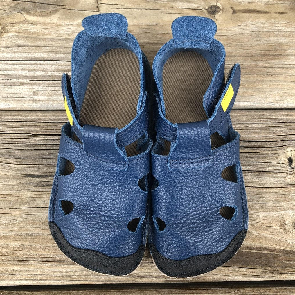 A pair of Tikki Nido sandals sitting on a wood deck in blue leather