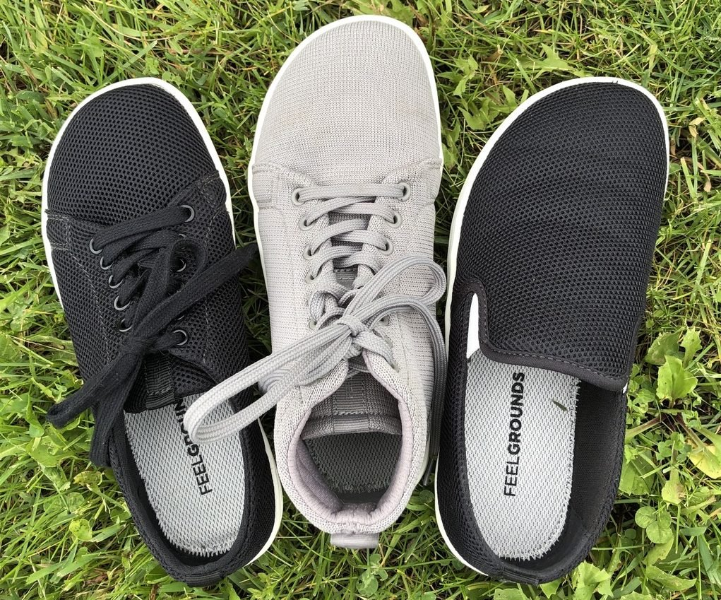 3 left shoes sitting side by side: All Feelgrounds casual barefoot shoe brand: The vegan Original sneaker in black mesh, the Highrise in grey knit Cloud, the Droptop in black mesh.
