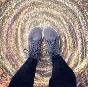 A top down image of a pair of feet wearing Feelgrounds vegan barefoot hightop sneakers
