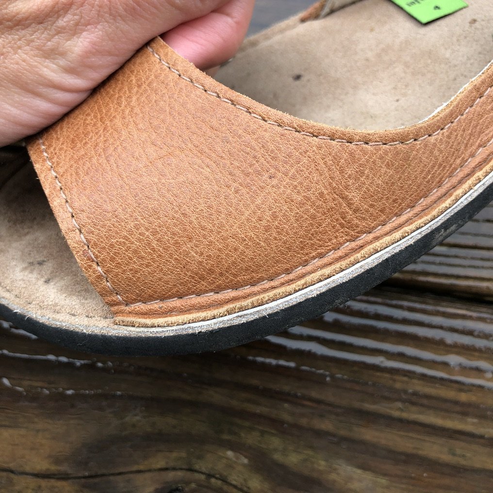 A closeup of a top stitch with raw edge on Botky Mechovky barefoot ballet flat.