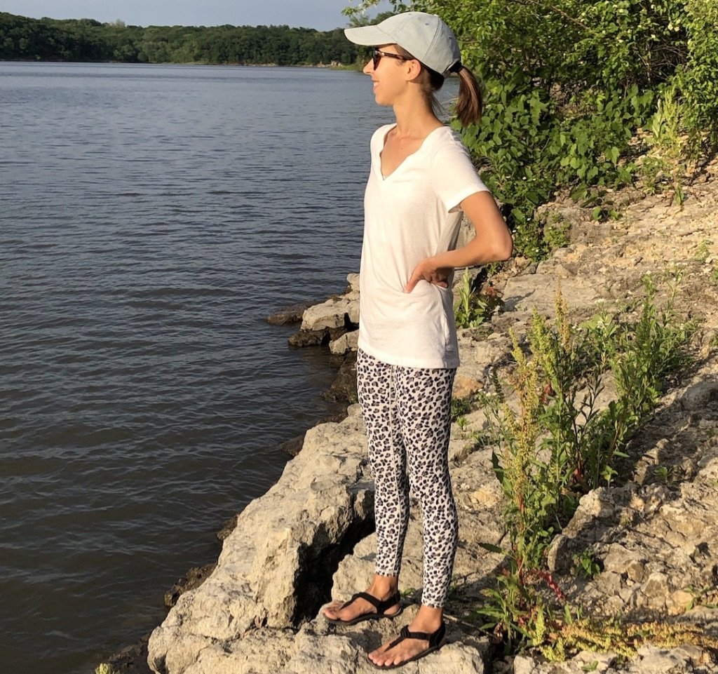 Woman shown standing on rocks overlooking a lake wearing Shamma Warrior Barefoot Running Sandals