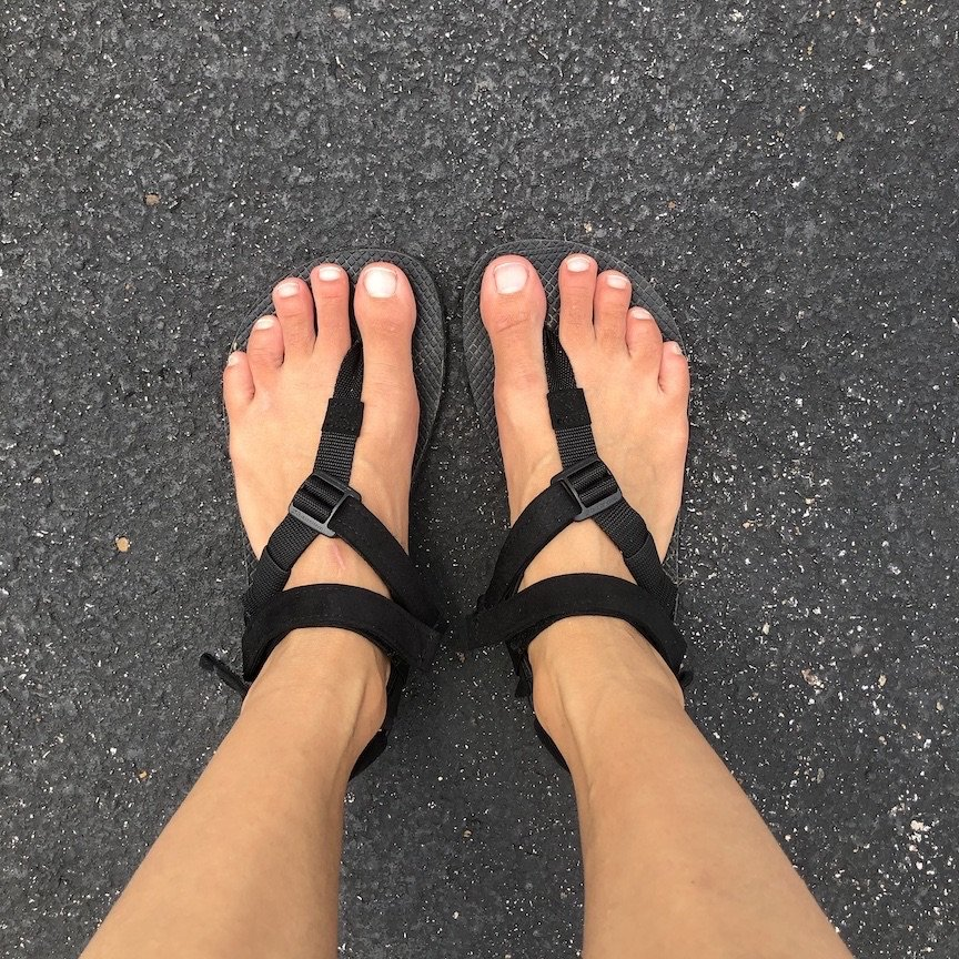 discount code for barefoot shoes at the black Shamma Warrior Sandals shown on feet with the Power Straps on, top down on view on asphalt