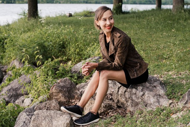 woman sitting on rocks outside smiling and looking to the side with obsidian vivobarefoot geo court sneakers on her feet and a black dress and tan leather jacket.