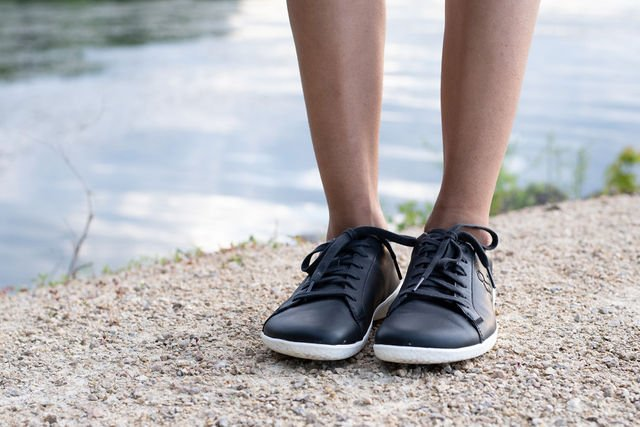 Close up of person wearing Vivobarefoot Geo Court SNeakers in black obsidian, front view outside on gravel with water in the background