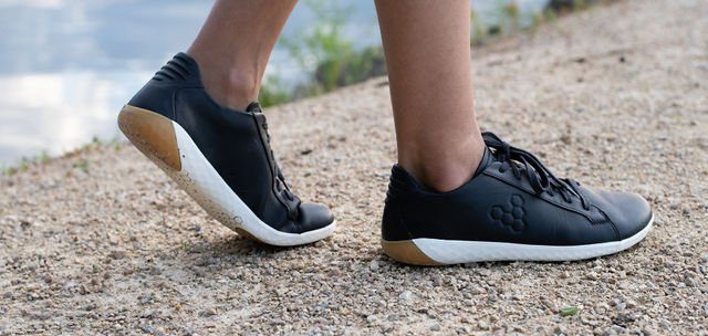 Cloes up of person wearing Vivobarefoot Geo Court SNeakers in black obsidian, side view outside on gravel with water in the background