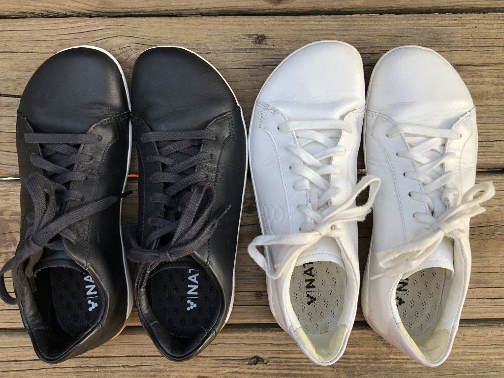Vivobarefoot Geo Court casual barefoot sneakers review shown in black and white sitting on a wood deck.
