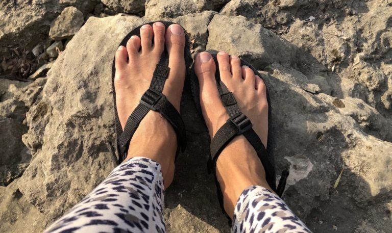 The black Shamma Barefoot Running Warrior vegan Sandals close up on feet top down view in nature, with rocks