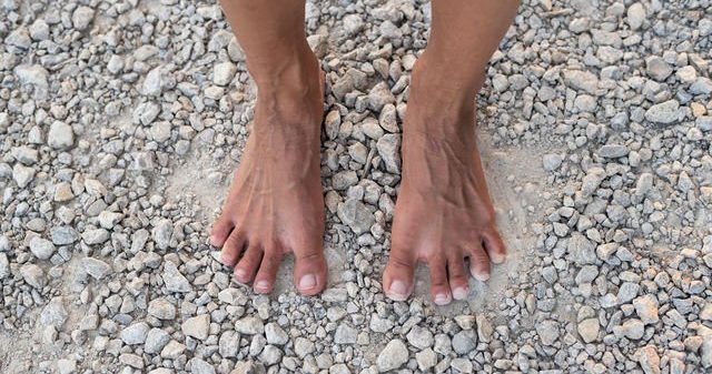 a close up town down shot of two bare feet standing on loose gravel with toes spread and muscles showing.