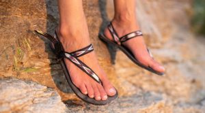 close up of feet dangling in front of rock with earth runners elemental sandals in tribal strap on