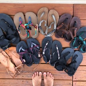 A top down view of 9 different pairs of sandals sitting on the ground.