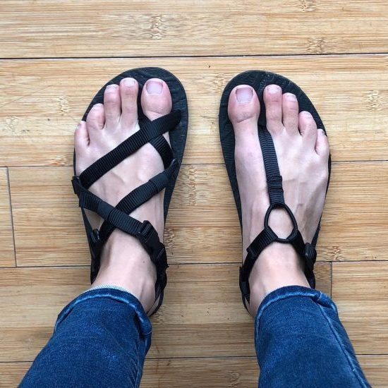 a top down view of a pair of feet with one foot in an Unshoes Uinta sandals (black) and the other in an Unshoes Keota Sandal (black).