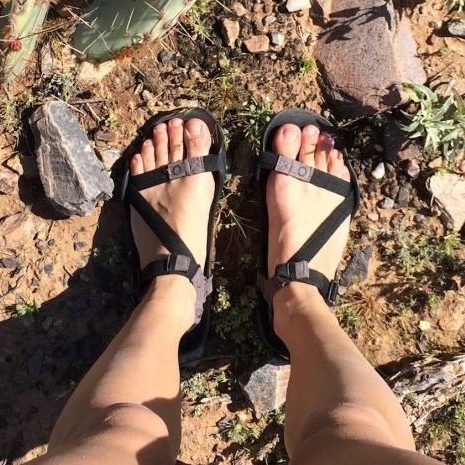Top down view of a pair of feet out in nature wearing Xero Z Treks in black