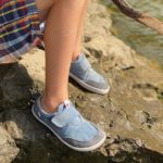 a close up of a child wearing splay athletics barefoot shoes for kids in blue