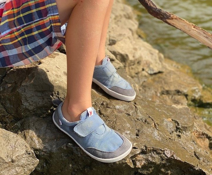 A close up of a boy wearing Splay Athletics minimalist shoes sitting on a rock