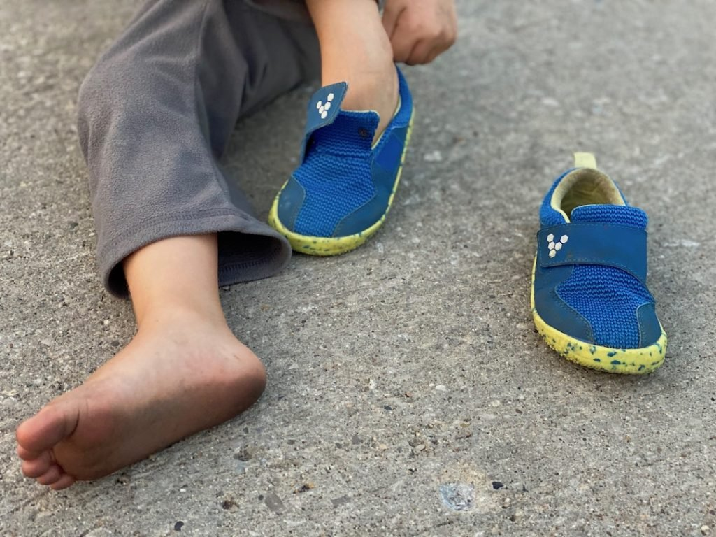 A close up of a small childs' feet putting on Vivobarefoot primus barefoot sneakers