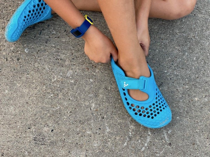 A child putting on a pair of Vivobarefoot Ultra water shoes