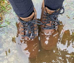 a close up of a pair of feet standing in a puddle of water wearing lems umber brown waterproof boulder boots