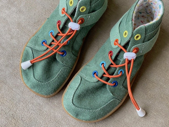 A close up of a pair of mukishoes barefoot shoes for kids in vegan canvas moss green color