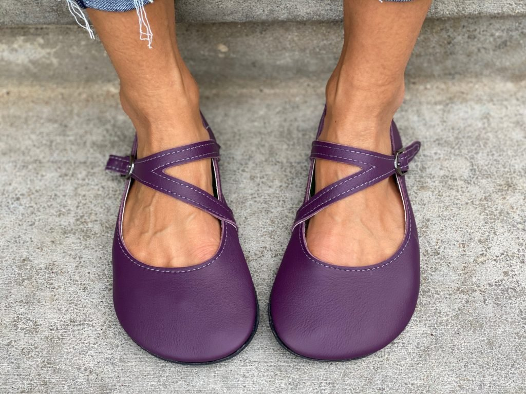 A front view of a pair of feet wearing the primal merry Jane in elderberry from softstar shoes on pavement