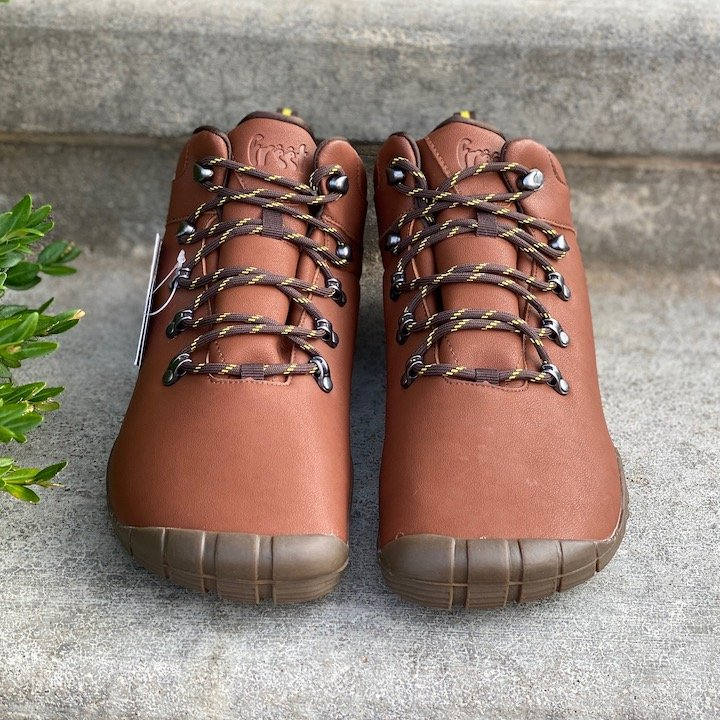 a close up of a pair of freet mudee vegan in brown sitting on concrete