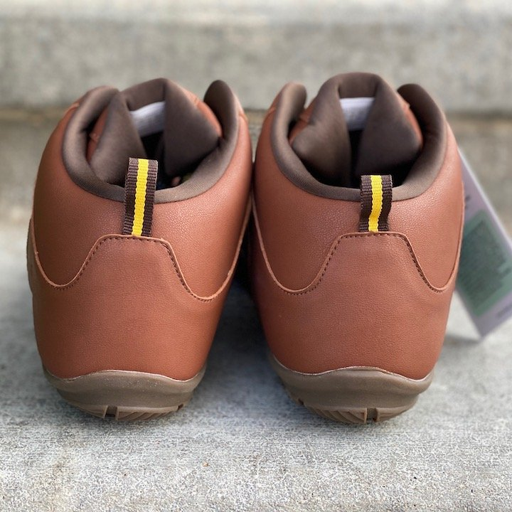 a close up of a pair of vegan freet mudee brown sitting on concrete with the heels visible for the best barefoot minimalist hiking boots review