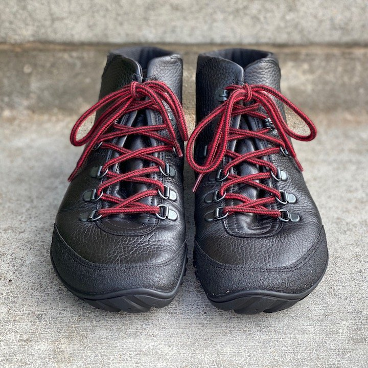 a close up of a pair of Joe nimble wandertoes in black sitting on concrete for the best barefoot minimalist hiking boots review