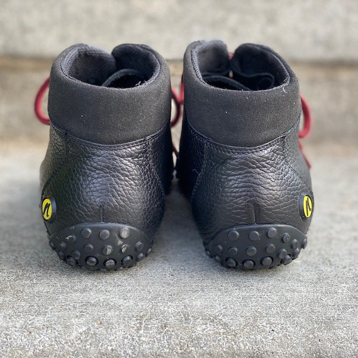 a close up of a pair of joe nimble wandertoes black sitting on concrete with the heels visible for the best barefoot minimalist hiking boots review