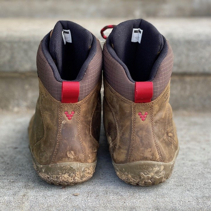 a close up of a pair of vivobarefoot tracker brown sitting on concrete with the heels visible for the best barefoot minimalist hiking boots review