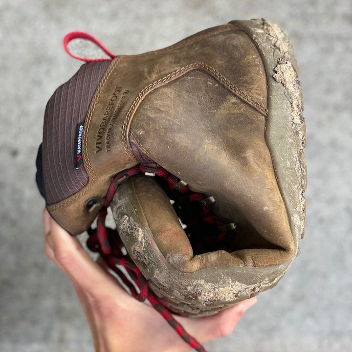 a close up of a hand holding a rolled up vivobarefoot tracker in brown for the best barefoot minimalist hiking boots review