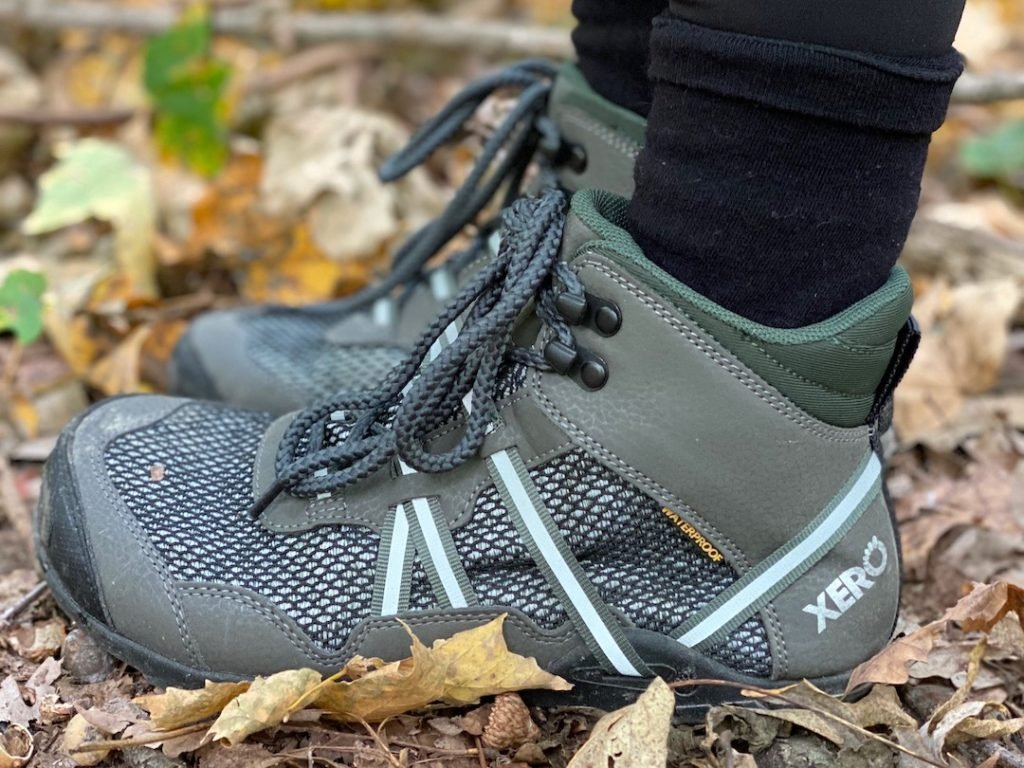 a close up of a pair of feet wearing the xero shoes waterproof vegan xcursion in green