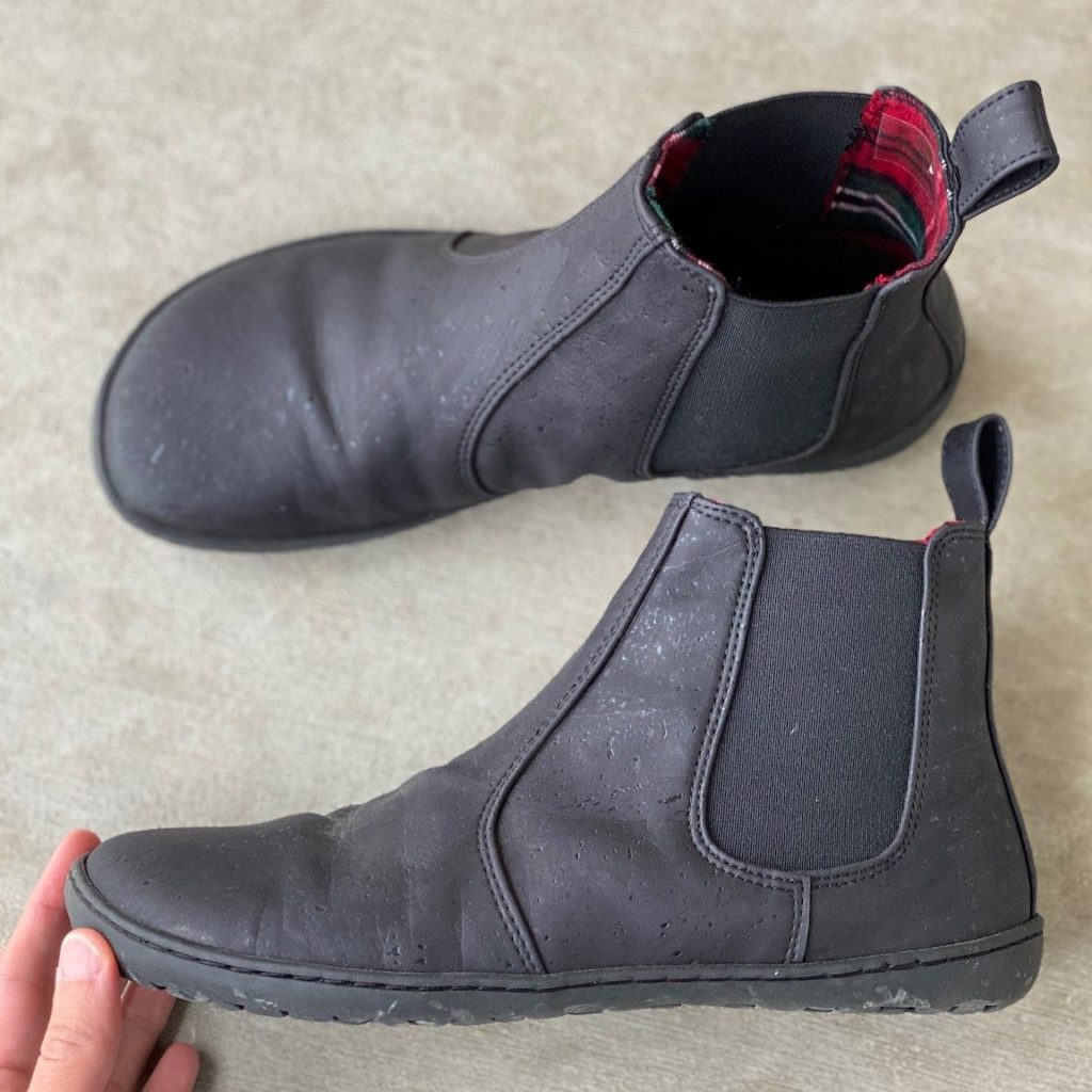 A close up or a pair of Mukishoes barefoot vegan black Chelsea boots from the side to show the zero drop outsole