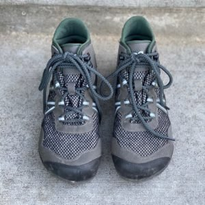 a pair of Xero shoes vegan Xcursion green sitting on concrete for the best barefoot minimalist hiking boots review