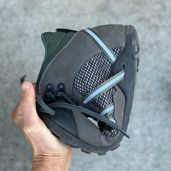 a close up of a hand holding a Xero shoes vegan Xcursion green rolled up over concrete for the best barefoot minimalist hiking boots review
