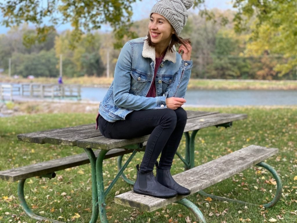 A woman sitting and smiling wearing Mukishoes vegan barefoot chelsea boot review
