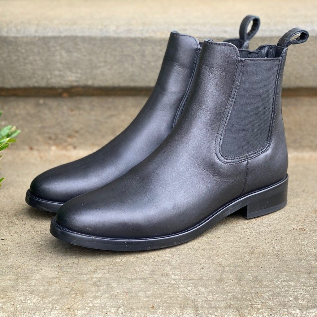 a side angle view of a pair of black traditional chelsea boots with an unhealthy heel and pointed toe by Thursday Boots - The Duchess