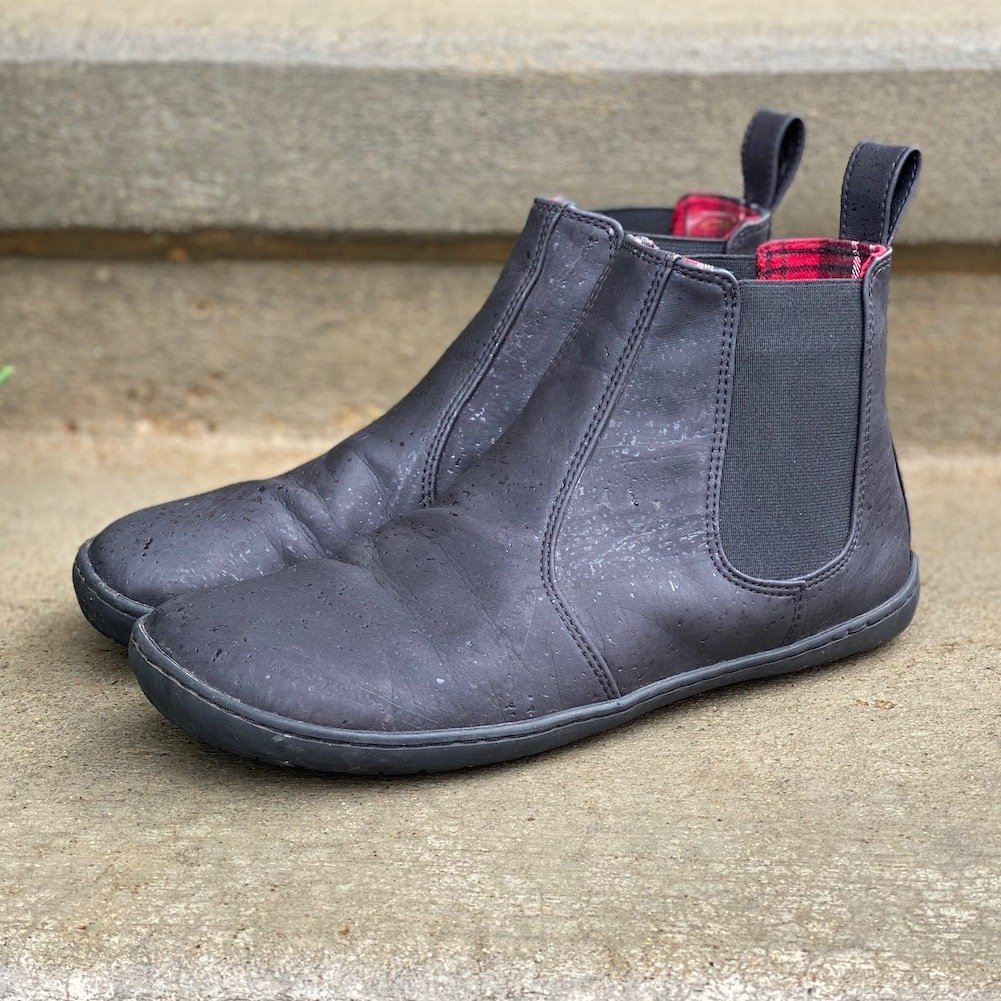 a close up review of the barefoot vegan chelsea boot from Mukishoes shown at a side angle sitting on concrete, made of black cork
