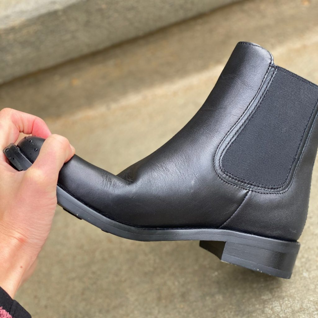 A hand trying to bend the Thursday Duchess Chelsea boot, but the sole is too stiff and it barely bends