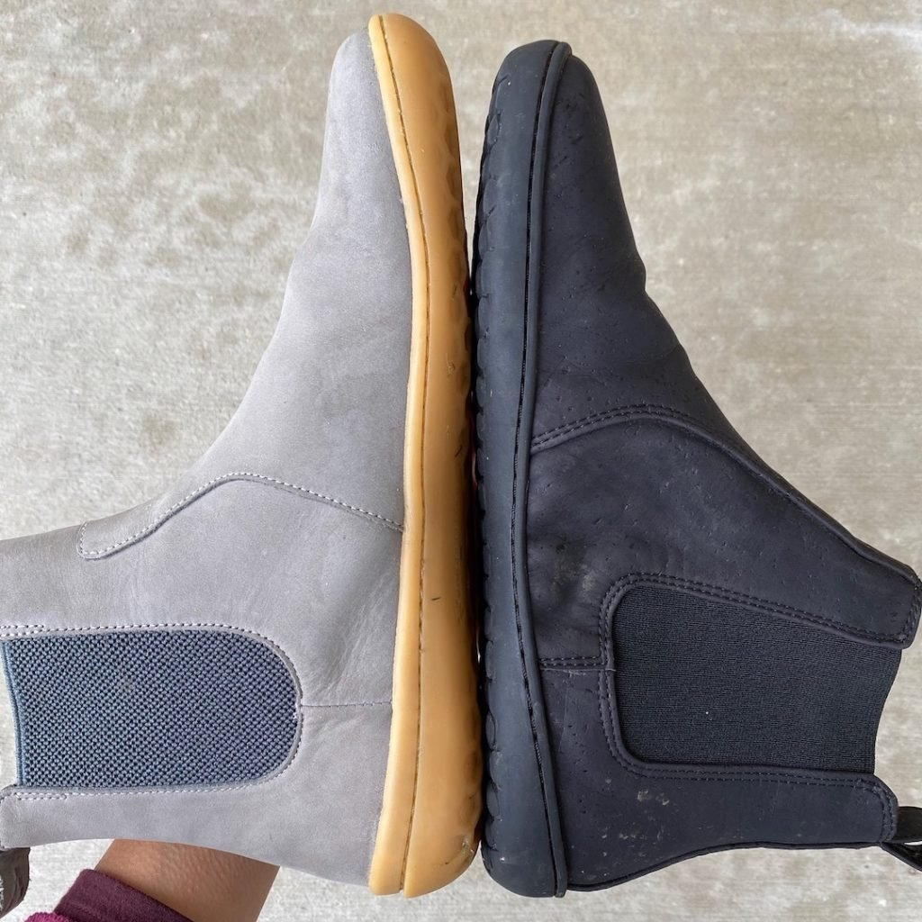 Two shoes held sole to sole to show that they are both zero drop barefoot shoes. On the left is the Vivobarefoot Fulham, and on the right if the vegan Mukishoes Chelsea boot made of cork