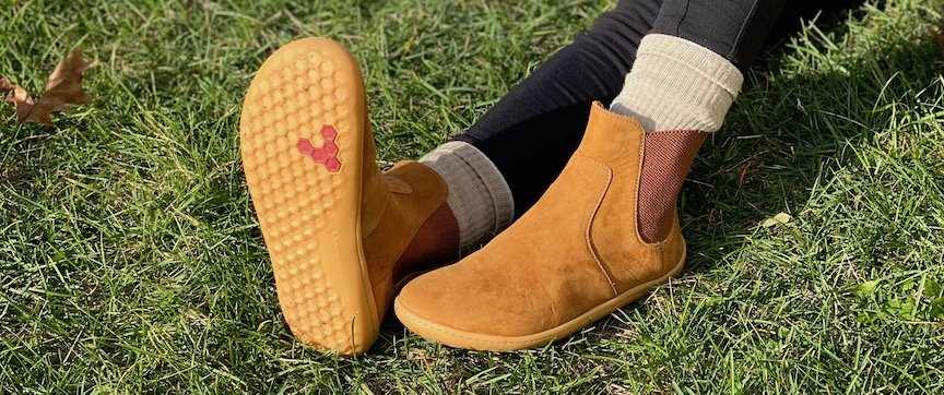 A close up of a pair of legs sitting on the ground with the feet wearing the Vivobarefoot Fulham review. One foot is on the ground and the other is pointing up so you can see the rubber outsole